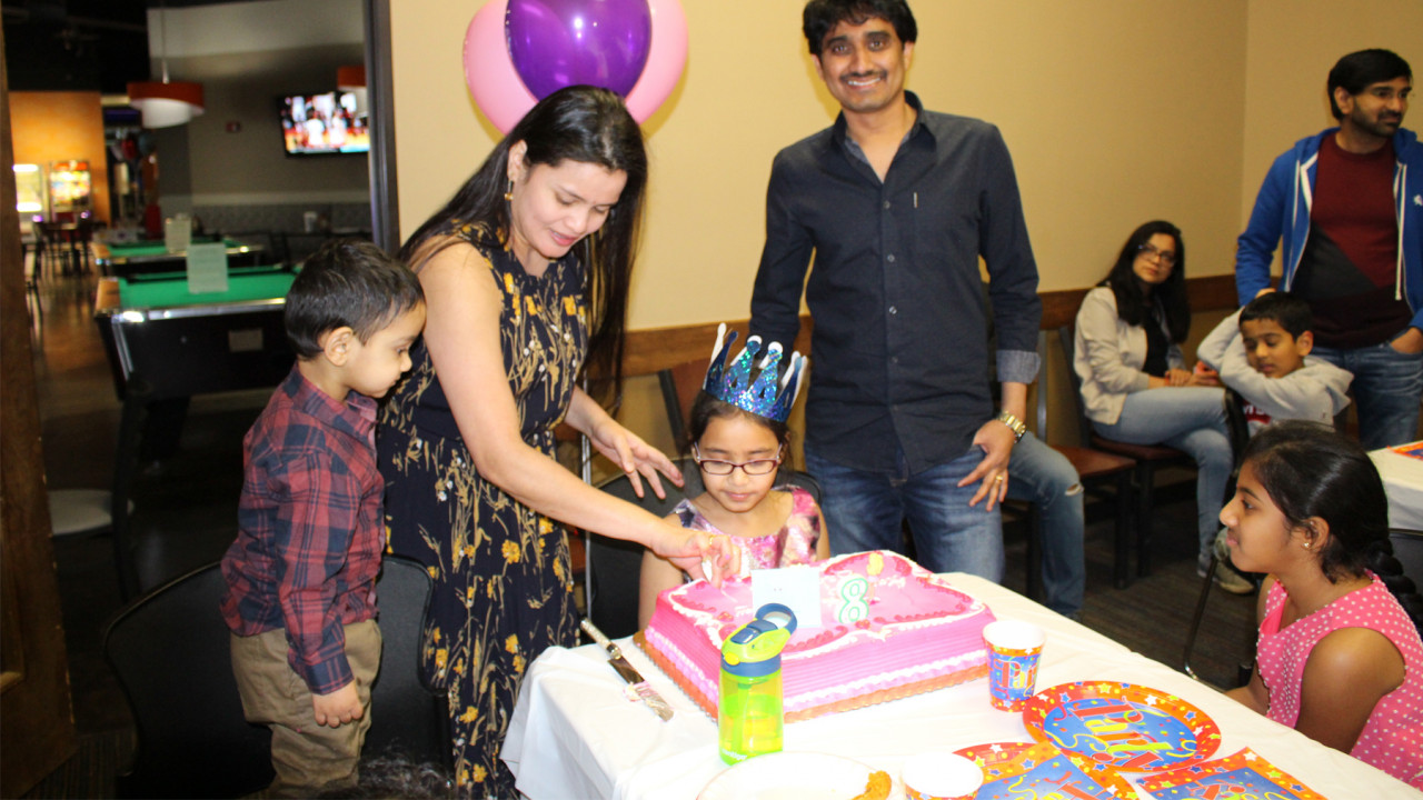 Parents cutting birthday cake for kids